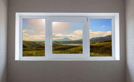Window view of a beautiful mountain landscape with field Standard-Bild