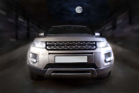 SUV moves on the road at night. Front view