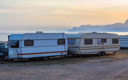 Camping trailers by the sea in summer at sunset