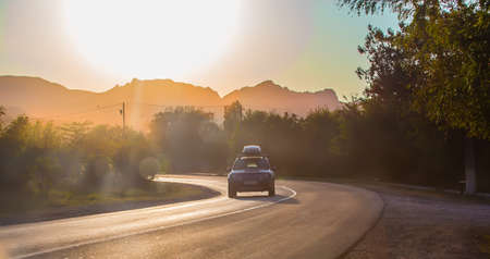 car moves on a road in the mountains at a bend in the sun at sunset Standard-Bild