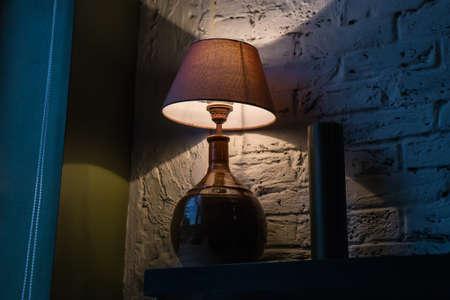 Stylish table lamp illuminating a brick wall and corner of the room Standard-Bild