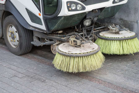 car for cleaning streets with rotating round brushes. Close-up, detail.