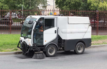 car for cleaning roads with round brushes on a city street. Standard-Bild