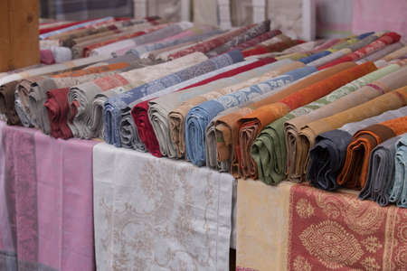 Rolls of various fabrics with drawings on the counter