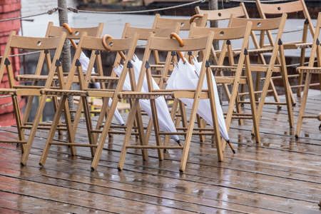 Wooden chairs and wet umbrellas in the street in the rain Standard-Bild