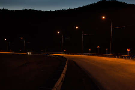 Road turn in the mountains at night lit by lanterns