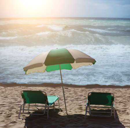Two sun loungers and an umbrella on a sandy beach by the sea at sunset