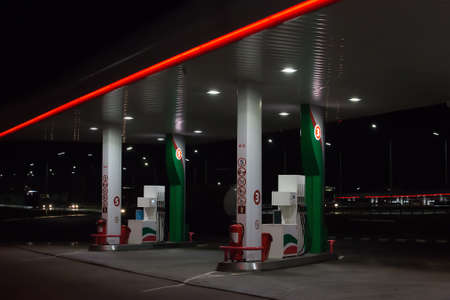 Gas station at night by the road illuminated by lanterns.
