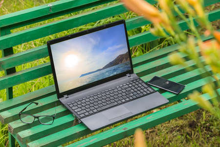 Laptop, glasses and smartphone on a bench in the summer garden Standard-Bild