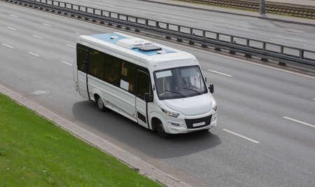 White minibus moves on a city street Standard-Bild