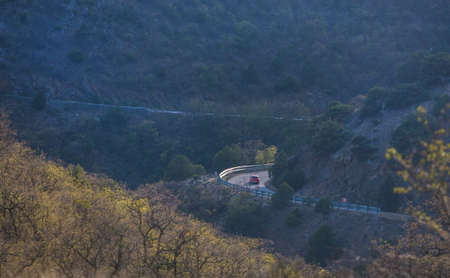 car moves along a winding mountain road in spring Standard-Bild