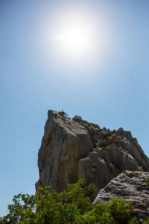 High cliff under a blue sky lit by sunlight