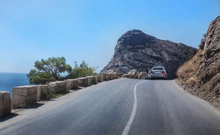 Car rides on a winding mountain road along the sea Standard-Bild