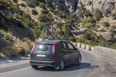 car with two bicycles on the upper trunk moves along a winding road in the mountains