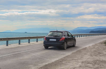 Car moves on the highway along the sea coast