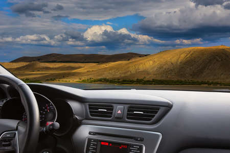 view from the car on a beautiful landscape with a river, mountains and a cloudy sky