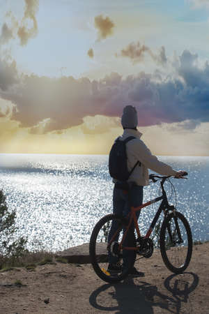 Girl with a bicycle near a cliff on the seashore at sunrise Standard-Bild