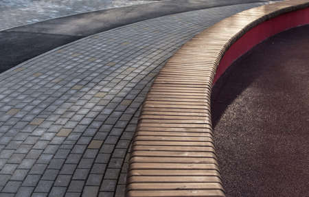 Winding sidewalk with a long wooden bench at the playground