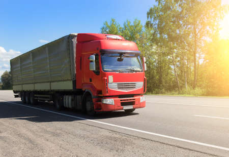 Big truck semi-trailer moves on a suburban highway