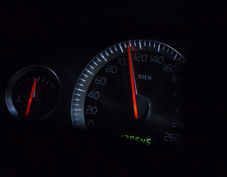 Car speedometer and temperature gauge on a dark background close-up.