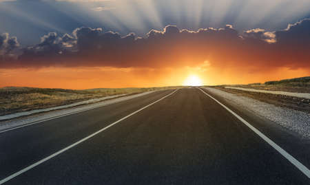 Road lit by the sun at sunset in the cloudy sky