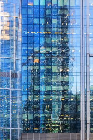 Glass Facade of a modern skyscraper with a reflection of a high-rise building