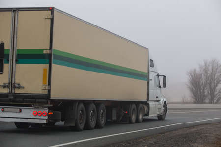 Truck Drives on a Suburban Highway in the Fog Standard-Bild