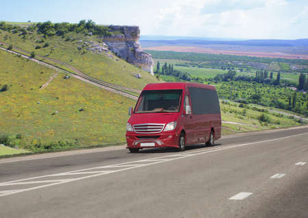 Red minibus moves on a road in the mountains on a summer day Standard-Bild