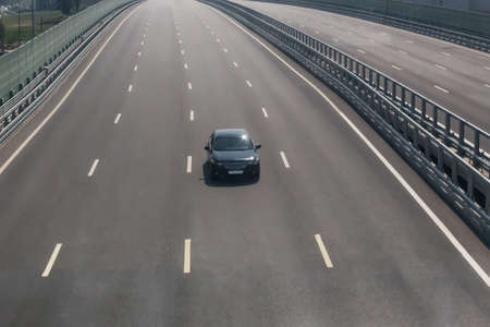 lonely car driving on an empty multi-lane highway