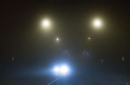 Thick fog on a country road lit by street lamps