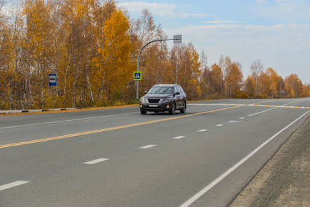 Car moves along a suburban highway along a yellow autumn forest