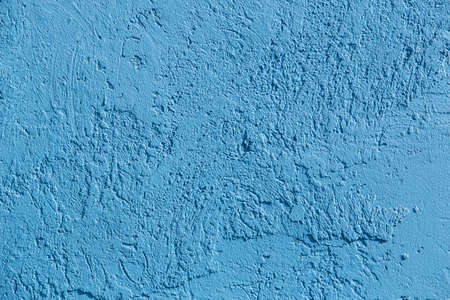Roughly plastered wall painted with blue paint close-up background