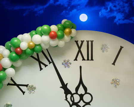 Few minutes before the New Year on the dial of a clock decorated with snowflakes and balloons against the background of a moonlit night