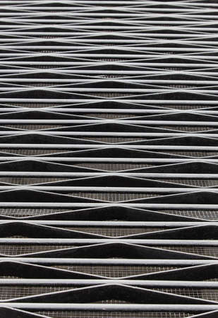 Decorative black lattice of metal rods and stripes close-up background