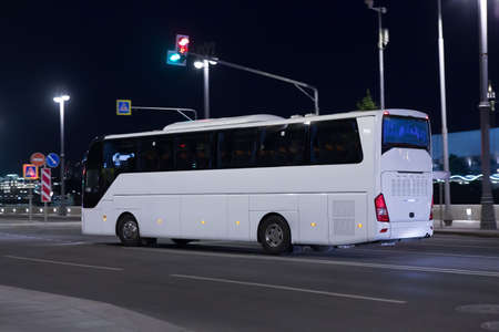 Tourist bus moves at night along the illuminated city street