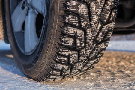 Car wheel with winter studded tread on snowy road. Close-up detail. Standard-Bild