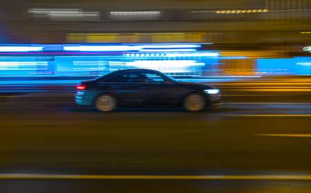 Black car drives along a city street at night. Blurry motion.