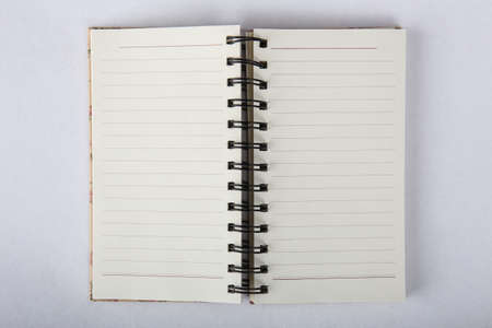 Opened paper notebook on blank pages on white background close-up