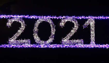 2021 Glowing in the dark garland in the New Year. Close-up, black background