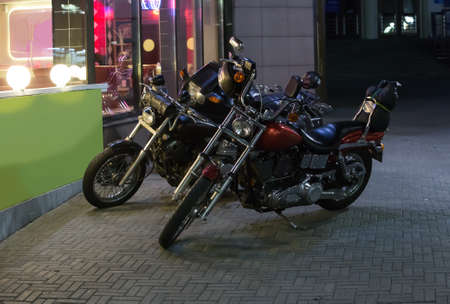 Motorcycles in the parking at night by the bar