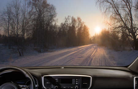View from the car on snowy winter road in the forest at sunrise
