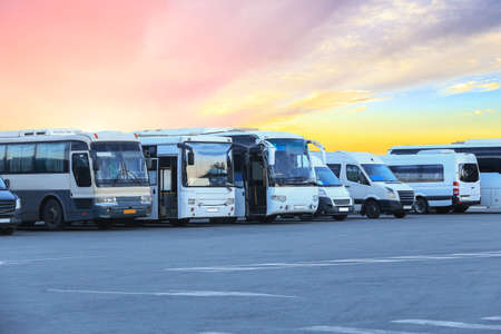 Buses in the parking lot of the bus station on the background of a beautiful sky at sunset Standard-Bild
