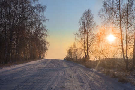 Winter snowy road in the morning at sunset landscape Standard-Bild