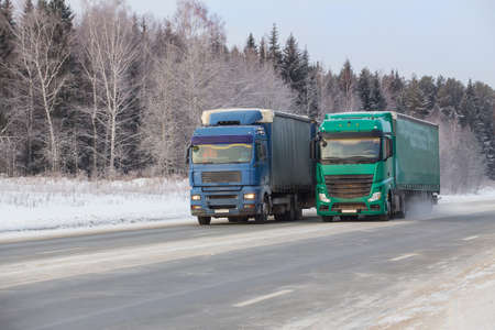 Trucks move in winter on a snowy road along the forest Standard-Bild