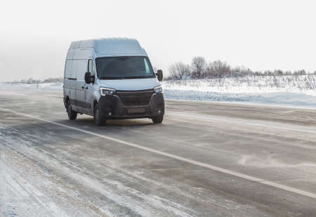 Minivan moves in winter on snow-covered road lit by the sun