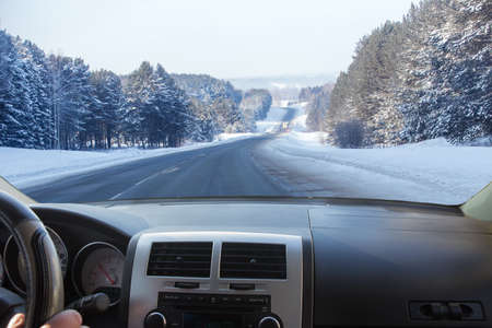 view from the car on a winter snow-covered country road along the forest.