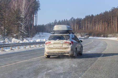 car moves in winter on a snow-covered country road lit by the sun. Winter travel. Standard-Bild