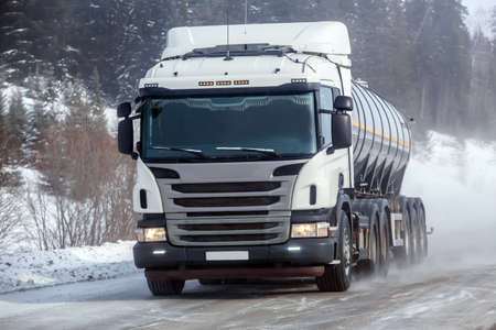 fuel truck moves on a winter snow-covered road outside the city