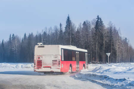 Bus moves in winter on a snow-covered road along the forest Standard-Bild