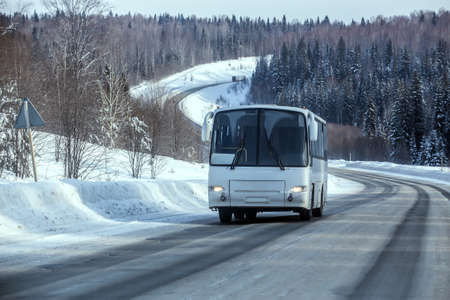 Bus moves in winter along a snow-covered winding country highway along the forest.
